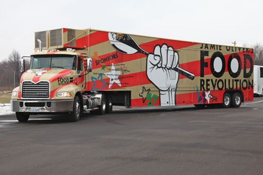 "Here's a photo of Jamie Oliver's new mega-food truck designed pro bono by architect David Rockwell's Rockwell Group. And more than just a food truck slinging tacos, it's actually a ""mobile teaching kitchen."" It's designed to ""create an immediate, unexpected spectacle"" at schools, street fairs, and farmers markets in that it can ""push out laterally for events"" making room for both an ""expo kitchen"" and eight separate cooking stations http://food-trucks-for-sale.com/"
