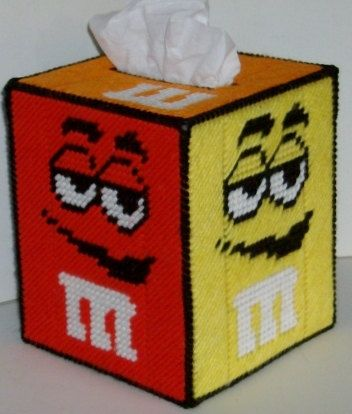 Everyone loves M & Ms. Heres a perfect way to add a splash of color to any room, childs room, rec room, pool side or patio, bar, or family room. This is very popular and a great way to have a tissue handy. All four sides are a different color and have different faces. Top is orange with the initial M. Lettering is done in white and it is stitched together with black. Fits a regular size boutique style tissue box. A new box of tissues will be included! Made of 4-ply acrylic yarn over pla...