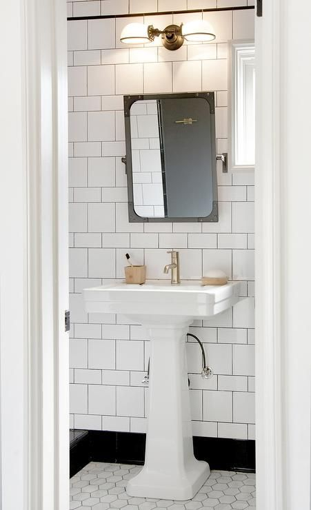 Black and white bathroom features a Restoration Hardware Industrial Rivet Flat Mirror - Pivot lit by a Vintage English Oval Double Sconce placed over a white pedestal sink atop a large marble hex tiled floor.