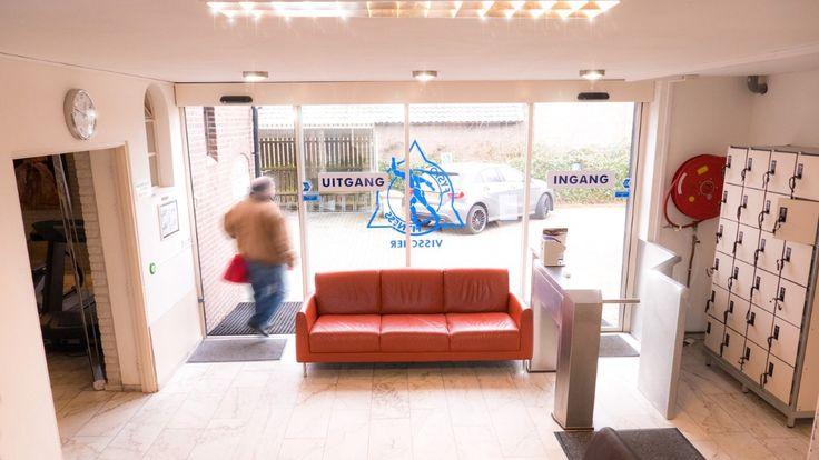 """""""De oplossing kwam in een volledige glazen pui met ranke aluminium profielen en ruimte besparende en geruisloze schuifdeuren. Door deze materiaalkeuze is er veel meer lichtval wat zorgt voor een open uitstraling en een mooie natuurlijk verlichte lounge. Middels de robuuste, waterdichte en verlichte aanraakschakelaars kan men nu moeiteloos naar binnen en naar buiten. De brede schuifdeuren maken de entree tevens rolstoeltoegankelijk..."""""""