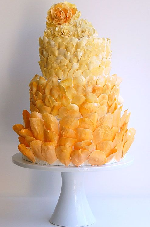 Hundreds of orange and yellow petals add rich texture to  this three-tiered wedding cake || Colin Cowie Weddings