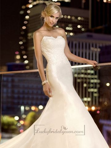 This fit and flare designer wedding dress in taffeta features lace appliques on the bodice and scalloped lace details on the sweetheart neckline and hem. The full skirt extends into a chapel train.
