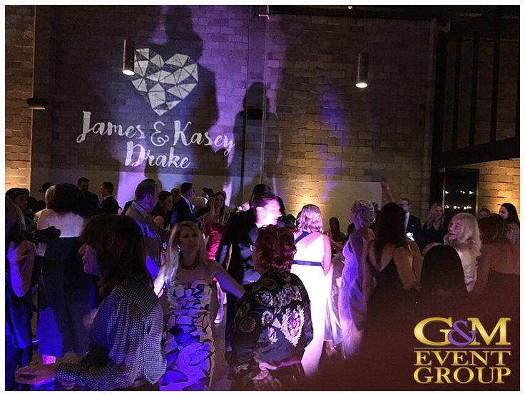 Kasey & James' wedding @ the Joinery West End - Wedding Cake | Wedding DJ + MC + Lighting | Custom Monogram | Warm White & Purple Uplighting #warehousewedding #uplighting #weddinglighting #custommonogram #weddingdj #weddingmc #gmeventgroup