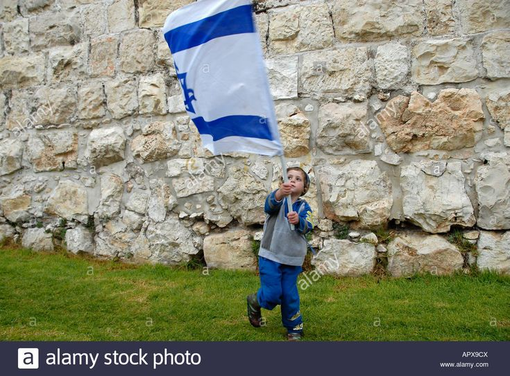 Download this stock image: Young religious Jewish boy waves the Israeli flag in front of the ancient walls of the Old city in Jerusalem Israel - APX9CX from Alamy's library of millions of high resolution stock photos, illustrations and vectors.