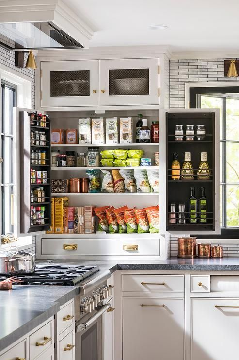 White cabinets accented with metal mesh doors are located above a well organized snack cabinet fitted with spice racks built into the doors and finished with brass hardware.
