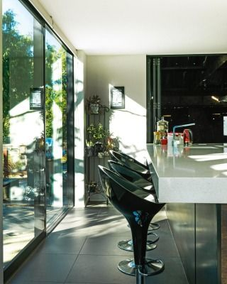 Large sliding doors open from the kitchen bar to an alfresco breakfast area.