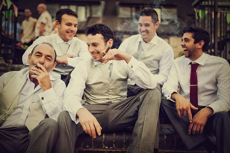 Groomsmen smoking cigars at the end of a wedding