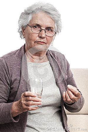 Old sick woman taking drugs. A glass of water and a pill in her hand. Isolated against white background.