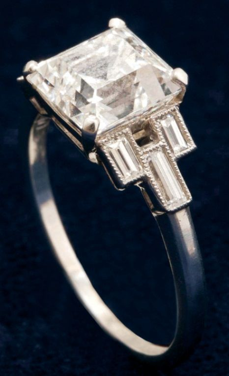 An Art Deco Asscher-cut diamond engagement ring set in platinum, with baguette and millegrain diamond shoulders. American, circa 1925. #ArtDeco #ring