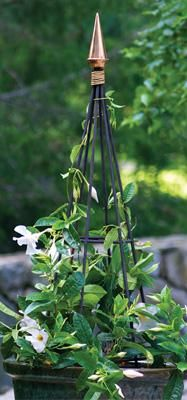 """Finial Obelisk - This magnificent obelisk is crafted from heavy-gauge steel and crowned with a polished copper Finial ornament to form a unique trellis support for flowers and vines. 46 1/2"""" H, 11 3/4"""" diameter.Designed to patina to a natural rust finish."""