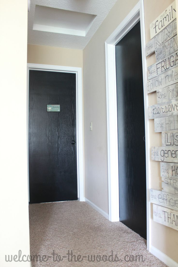 Hallway decor ideas. White trim, black doors, and a tall skinny wood pallet sign.