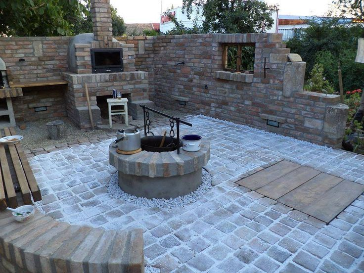 An awesome back yard patio with a bbq, a smoking pit, and a nice cauldron in the middle for making beans or bbq sauce.