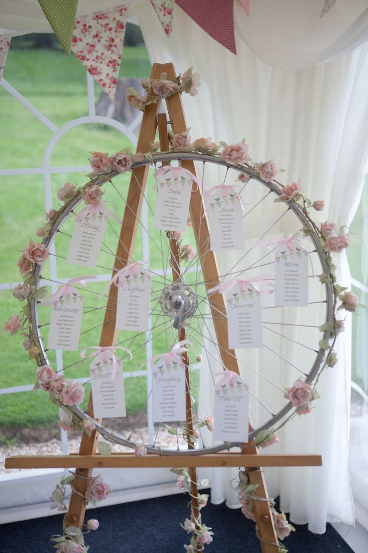 Vintage bunting luggage labels wedding table plan using a bicycle wheel.