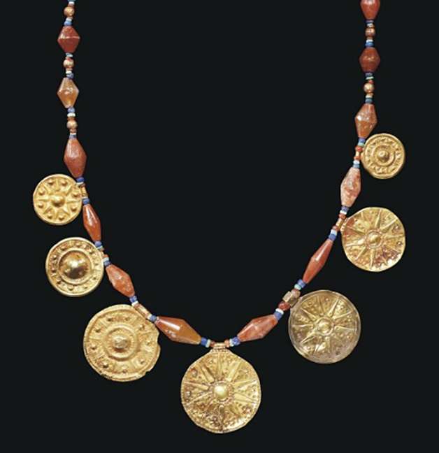 A WESTERN ASIATIC GOLD AND STONE BEAD NECKLACE   CIRCA 1200-800 B.C.   Composed of biconical carnelian beads interspersed with small lapis lazuli and turquoise spacers and gold beads, centered by six gold disk pendants stamped with stars; strung with a modern hook-and-loop closure  34½ in.