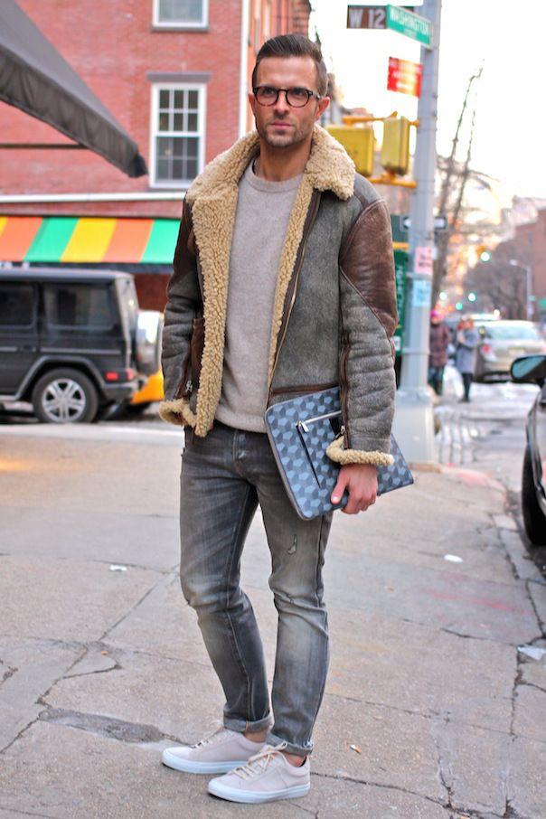 Shop this look on Lookastic:  http://lookastic.com/men/looks/crew-neck-sweater-shearling-jacket-zip-pouch-jeans-low-top-sneakers/8736  — Grey Crew-neck Sweater  — Grey Shearling Jacket  — Blue Geometric Leather Zip Pouch  — Grey Jeans  — Grey Canvas Low Top Sneakers
