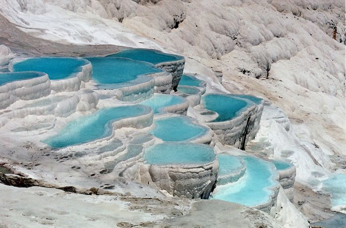 "Pamukkale  Pamukkale, or ""Cotton Castle"", is a series of shimmering snow-white terraced travertines, which cascade down the mountain side slopes, formed by limestone-laden hot springs. The passing of time has yielded stalactites, potholes and magical fairy-tables. The thermal water is also reputed to have healing properties. Paddling in the little pools on the plateau is possible and exhilarating. There are also other hot pools in the area, supplied by the natural springs, where you can swim…"