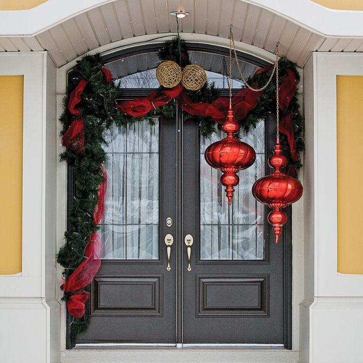 L'architecture de cette maison aux dimensions généreuses est mise en valeur par d'élégantes décorations. Ces ornements confectionnés sur une base de sapinage artificiel ont fière allure sur la toile de fond d'un jaune lumineux. Une guirlande rouge, entrelacée entre les branchages, établit une belle continuité entre les parures des fenêtres, de la galerie et de la porte d'entrée. Deux boules géantes sont les vedettes de l'entrée. D'un rouge brillant, elles offrent un a...
