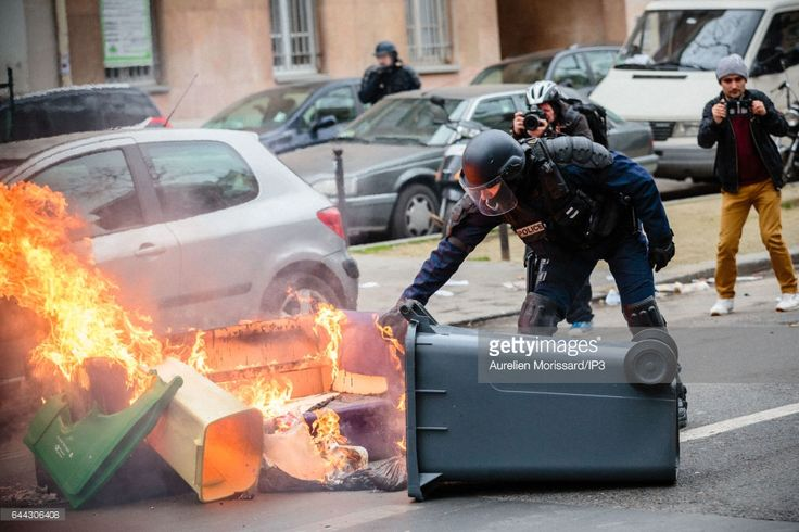 A police officer handles a burning rubbish bin after clashes between police and rioters took place while High school students gather for a demonstration to support Theo and against Police violence at Place de la Nation on February 23, 2017 in Paris, France. Theo, 22, was arrested by four policemen in the Rose des Vents district of Aulnay sous Bois in Seine Saint Denis on Thursday, February 2nd. He was later admitted to hospital, suffering serious injuries after allegedly been sodomized by…