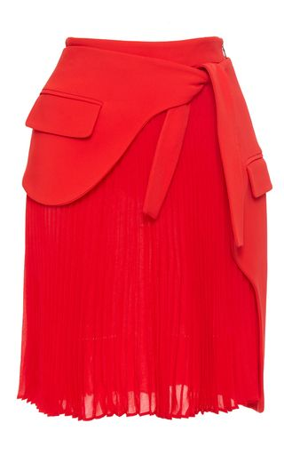 This **Antonio Berardi** mini skirt features a high waist with a tie, patch pockets, and all over pleats.