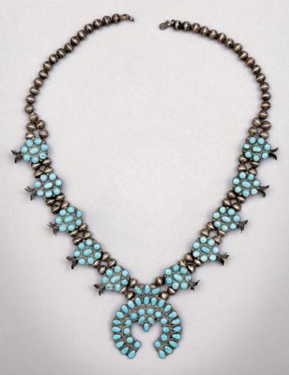 * Collier de turquoises Zuñi. Nouveau Mexique, U.S.A. - ca. 1890  finement serti de nombreuses turquoises. De chaque côté, cinq pièces incrustées (ornées de «fleurs de courge») s'intercalent avec des grosses perles d'argent (en séries de quatre). Le pendentif en croissant, appelé «Naja», arbore un très beau «cordage» d'argent.. Argent, turquoises, cordelette de coto