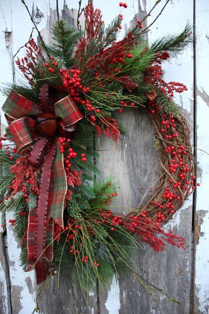 Ghirlanda natalizia composta da un corpo di rami secchi ricoperti in parte da rami di abete bacche e fiocchi
