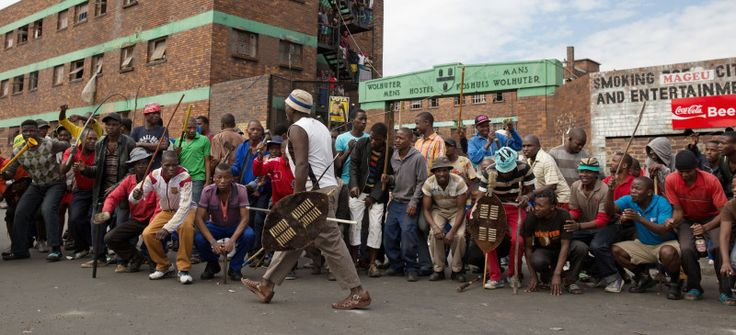 "Here we go again… | The Con  Main Image April 17, 2015. An Induna commands a mob outside ""Jeppe"" Hostel in Johannesburg. Picture: JAMES OATWAY    James Oatway is an independent South African photographer.     The former Chief Photographer and Picture Editor of the Sunday Times newspaper, he has been freelancing since 2016. He has covered many important stories in South Africa and abroad, but has a special interest in telling under-reported stories in Africa."