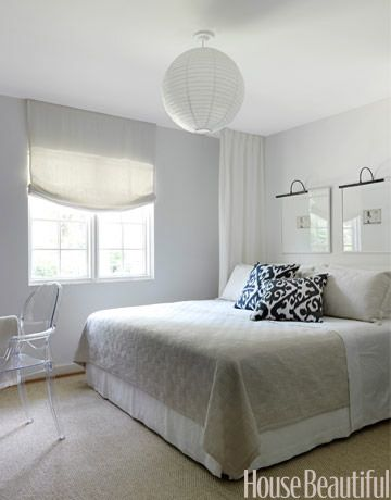 This modern bedroom by designer Lindsey Bond opts for minimal white and neutrals with statement patterned pillows and an eccentric fixture. | housebeautiful.com Photo by Jonny Valiant