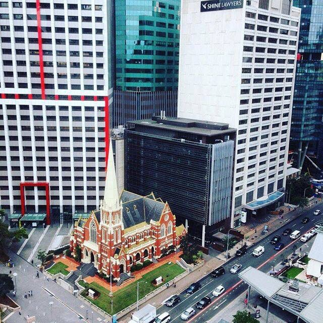 The beautiful Albert Street Uniting Church stands out surrounded by modern buildings in this picture.