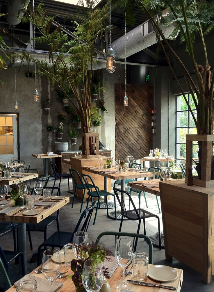 Love the Edison pendant lights. Great detail with the exposed bolts at ends of table tops. Sweet table bases, I like how they have a greyish color instead of black. The plants/green make the look. Diagonal plank wood feature wall is a nice detail. The cafe at Terrain at Westport.
