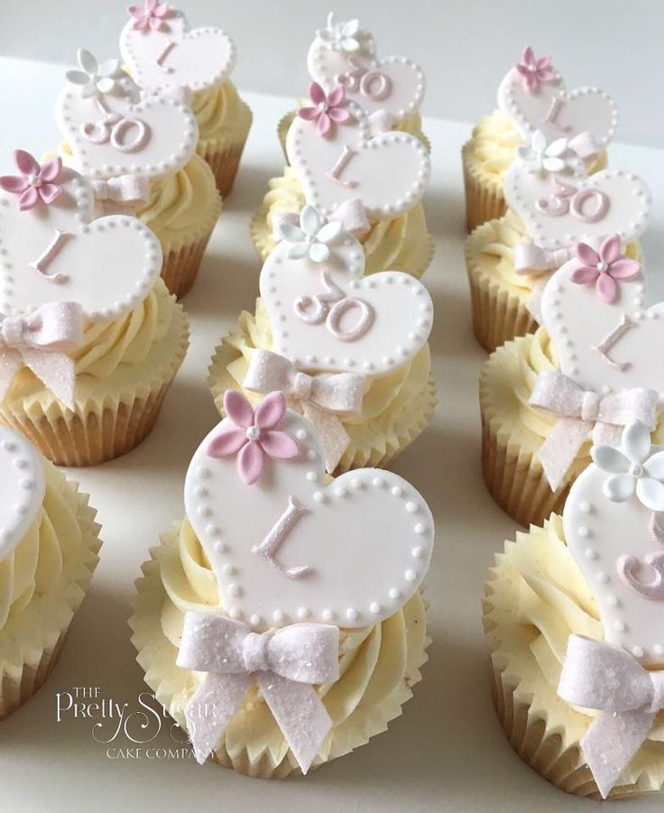 Pretty pink 30th birthday cupcakes with hearts and glitter bows