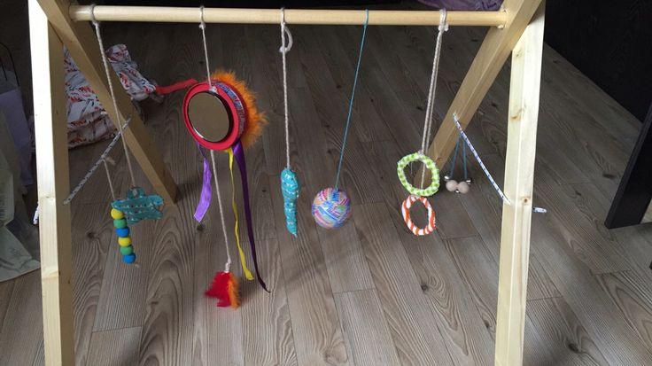 Zelfgemaakt : dit is de babygym die ik zelf heb gemaakt. Je legt de baby eronder en hij wordt geprikkeld om tegen het speelgoed te slaan, te schoppen of het vast te nemen  Wat hangt er aan: 2 grijp ringen, een bal met geluid in, een rammelaar van stof met een belletje in, een metalen doos met linten en veertjes aan + spiegel, een knisper bloemetje, houten balletjes in verschillende kleuren en  belletjes.