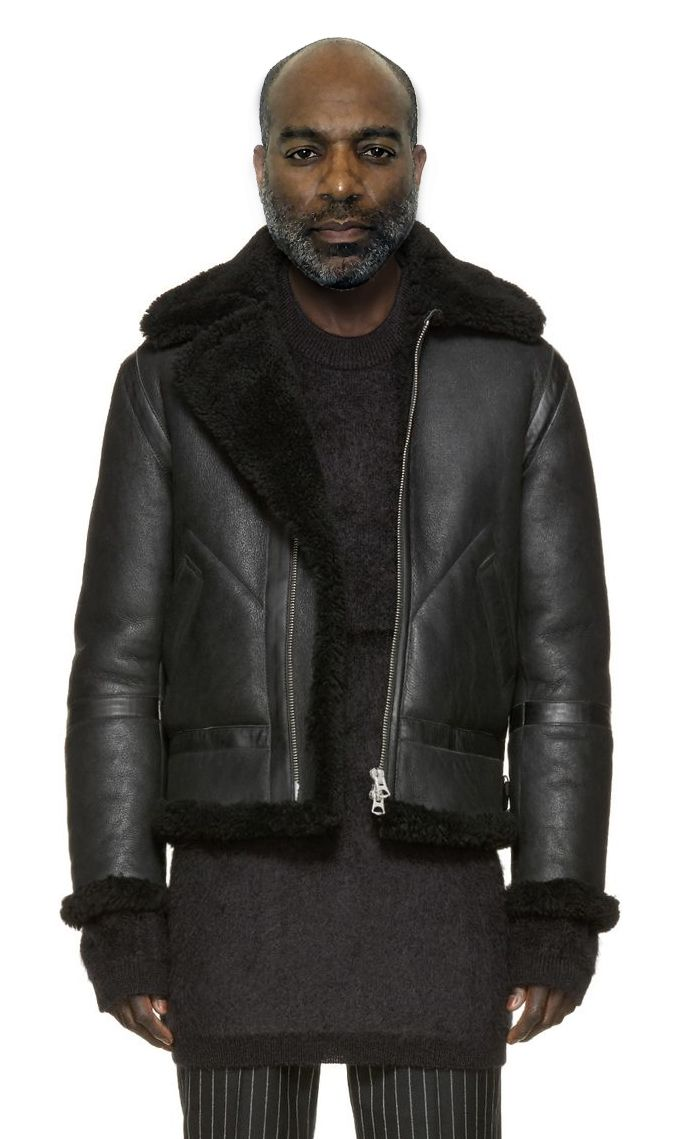 Indigo Denim & Shearling Jacket Long-sleeve lamb shearling jacket in black. Visible shorn wool at spread collar, cuffs and hem. Cinch strap with pin-buckle at collar base and at waist. Zipper closure at front. Buffed leather trims throughout. Eyelet vents at armscyes. Tonal stitching.                                                                                                                                                                                 More