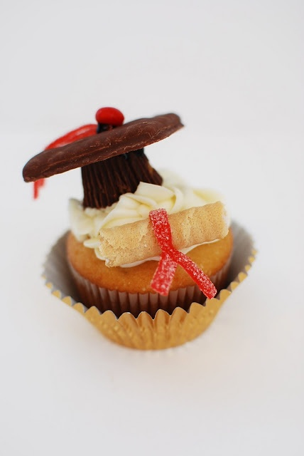 Graduation Cupcakes -- you will need:  Cupcakes with icing  Red hots or m  Square chocolate cookies  Fruit rollop or similar gummy strips cut into thin strips and 1 1/2 inches long  Waffle cookies or Oreo Funstix cut into 1 1/2-2  inch pieces  Reese's Mini Peanut Butter Cups  Decorating Gel or similar