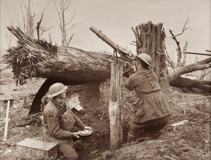 An Australian machine gunner has fixed his Lewis gun bipod on a tree stump and opens fire on German planes, Aug 1918. His feeder is ready with another pan magazine. The Lewis was quite effective against WW1 planes and their light structures.