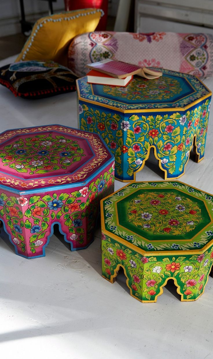 Set of 3 pressed wood tables in green, pink and blue lavishly painted with flowers and foliage. Hexagonal shaped tops with intricately cut-out legs. One fits inside the other and they can be stored away easily. Handmade - minor flaws in paintwork are part of the design. Fairtrade product.