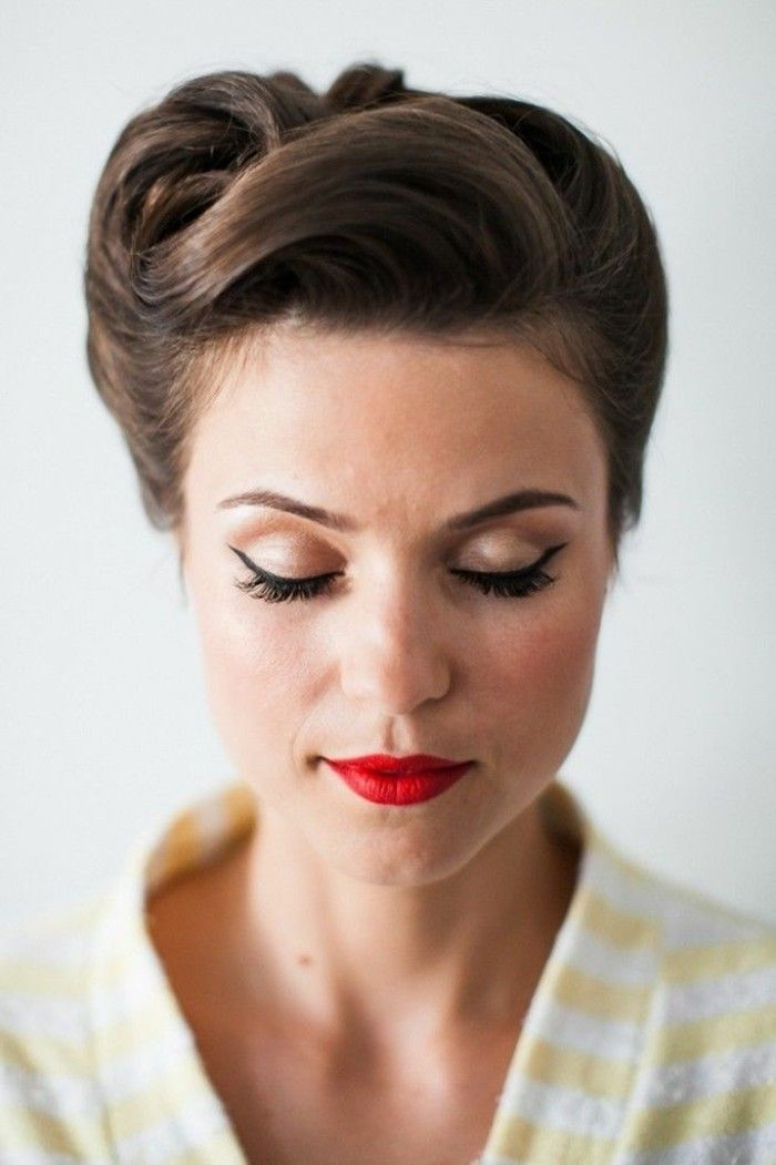 brunette woman with closed eyes, wearing eyeliner and red lipstick, retro updo hairstyle, yellow and white striped top