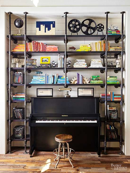 Industrial-chic shelves crafted from lumber and metal pipes collect books, photos, and storage bins filled with personal trinkets. A sleek piano takes center stage.