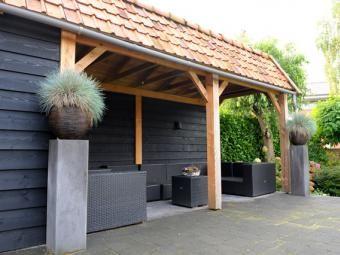 Sfeervolle overkapping gebouwd door hoveniersbedrijf De Bergden, uitgevoerd in zwart geverfd Zweeds Rabat, Douglas frame en dakbeschot van ruwe Douglas planken.
