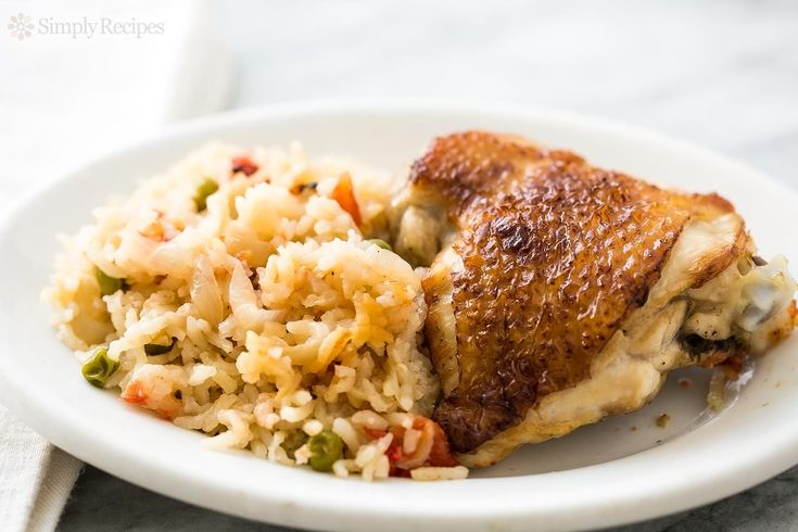 The BEST slow cooker chicken rice casserole! Sautéed onions, browned chicken thighs, with basmati rice, tomatoes, peas. The seasoning is PERFECT. #crockpot On SimplyRecipes.com