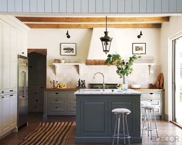 contemporary farmhouse kitchen.  exposed wood beams, open shelving, two-tone cabinets, and sleek, modern stools | laura resen