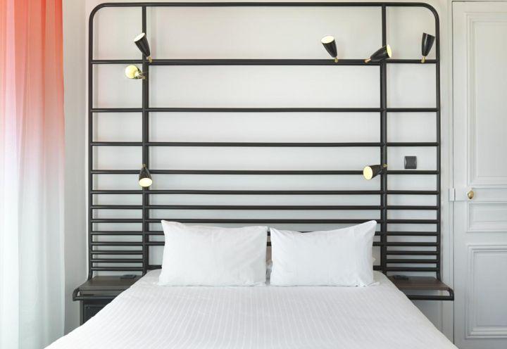 Tende in colore corallo e bianco per una delle 37 camere dell'albergo boutique La Demeure, di recente ristrutturato a Parigi da Flavie+Paul, duo di designers francesi che ha anche ideato i mobili su misura, a partire dal letto con testiera in tubolari di acciaio