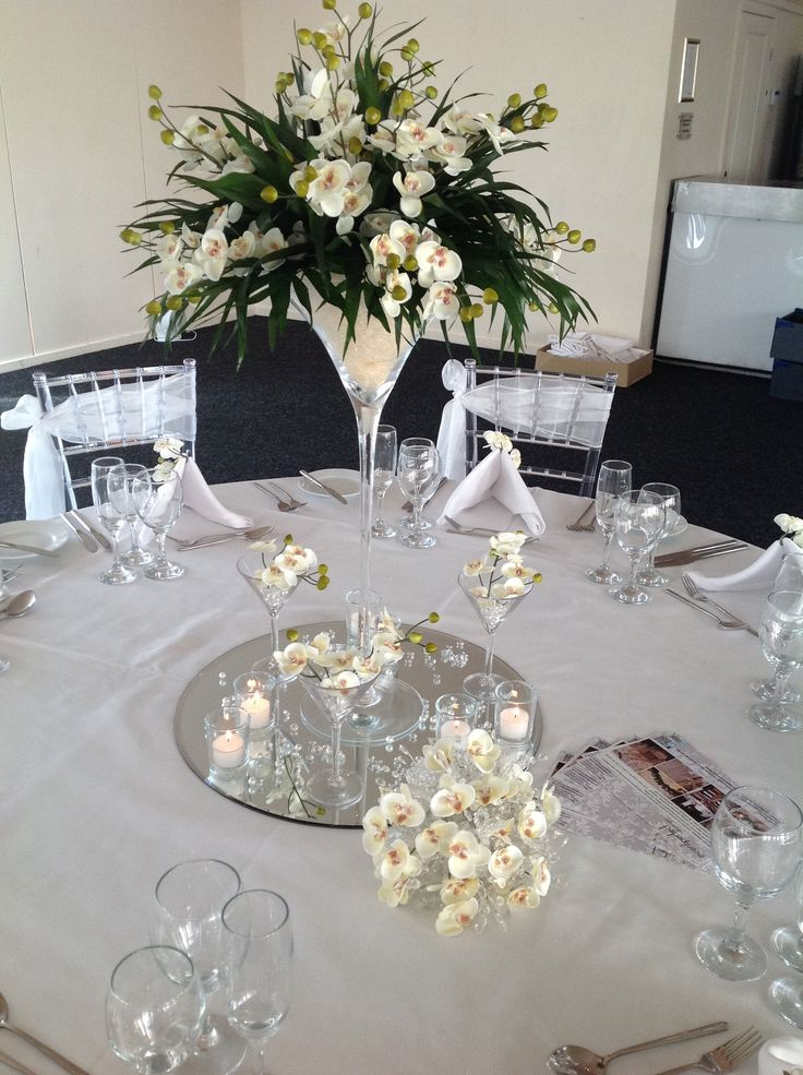 Floral arrangement set in a martini glass on mirror tile base with scatter crystals and petals.
