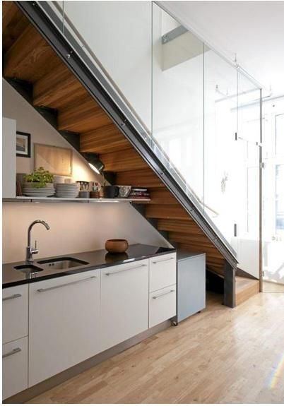 When space is tight, a clever strategy is to annex the area under a staircase. Here's a roundup of kitchens that maximize below-stairs space. Above: A