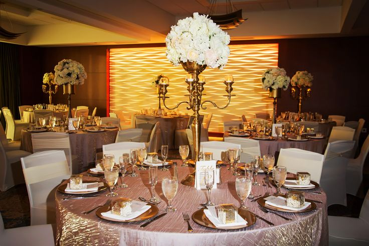 Elegant tall candelabra centerpieces and sequin tablecloths for a glamorous indoor ballroom wedding reception at the Westin Tampa Bay (Limelight Photography)