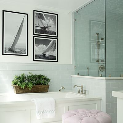 In the master bath, black-and-white sailing photographs and a striped rug enliven muted elements, like pale blue wain-scot and a pink upholstered ottoman. CoastalLiving.com