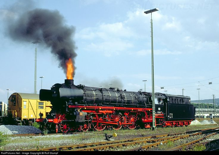 RailPictures.Net Photo: DB 01 1100 Deutsche Bundesbahn Steam 4-6-2 at Stuttgart, Germany -- Flames shoot out of the stack of oilburning Pacific 01 1100. The steam engine just had completed a fan trip from Nuremberg to Stuttgart and was tied up at Stuttgart. Upon restarting the oilburner flames shot through the tubes and eventually out of the stack. Look at the fireman leaning out of the window... That's quite a rare sight,