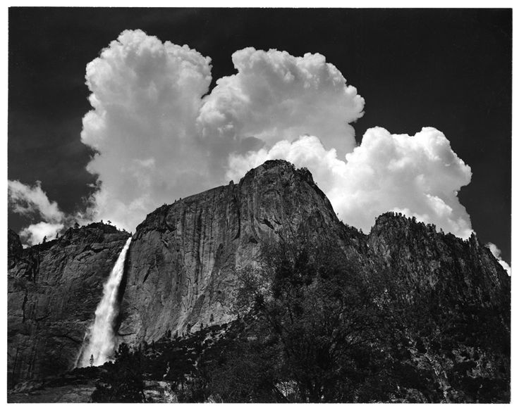 Ansel Adams- Black and White Photo. The way the cloud is coming over the mountain adds for a dramatic effect.