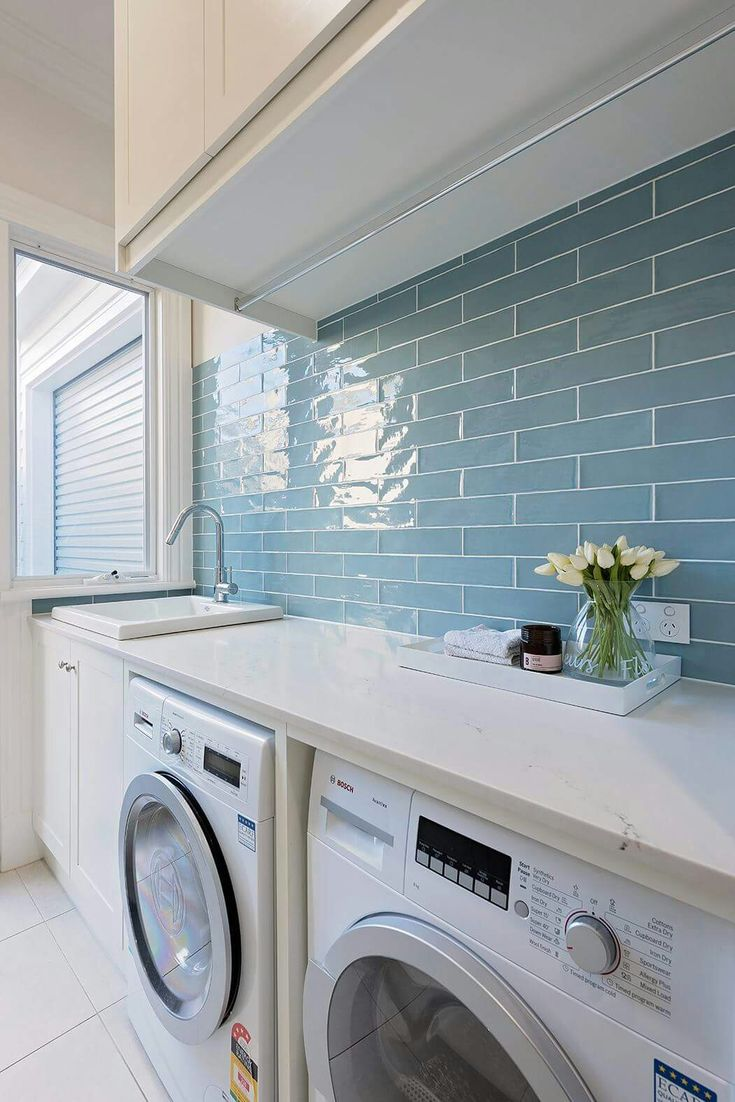 White laundry room with sky blue glass tile backsplash