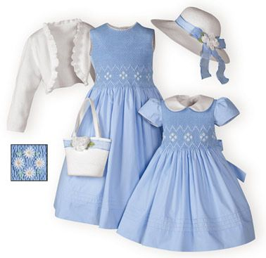 Pretty sister dresses of periwinkle pima cotton with finely hand-smocked bodices. White and yellow daisy embroidery. Decorative pleated hemline. Fully