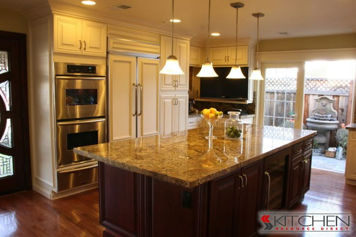 Traditional kitchen with white cabinets along the perimeter and mahogany stained cabinets on the island.